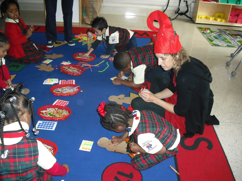 ELF staff member, Becky Collins, works on a holiday project with Kindergarten students.
